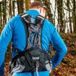 Homme qui utilise sont sac d'hydratation pendant un trail